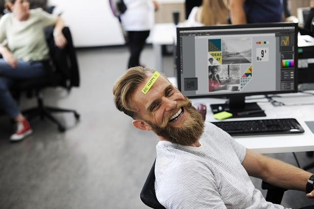 A man smiling among colleagues in the workplace