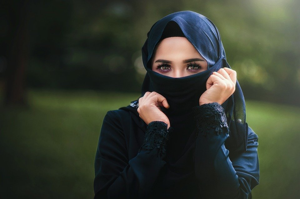 a woman dressed in a burka with her face cover, with only her eyes showing.