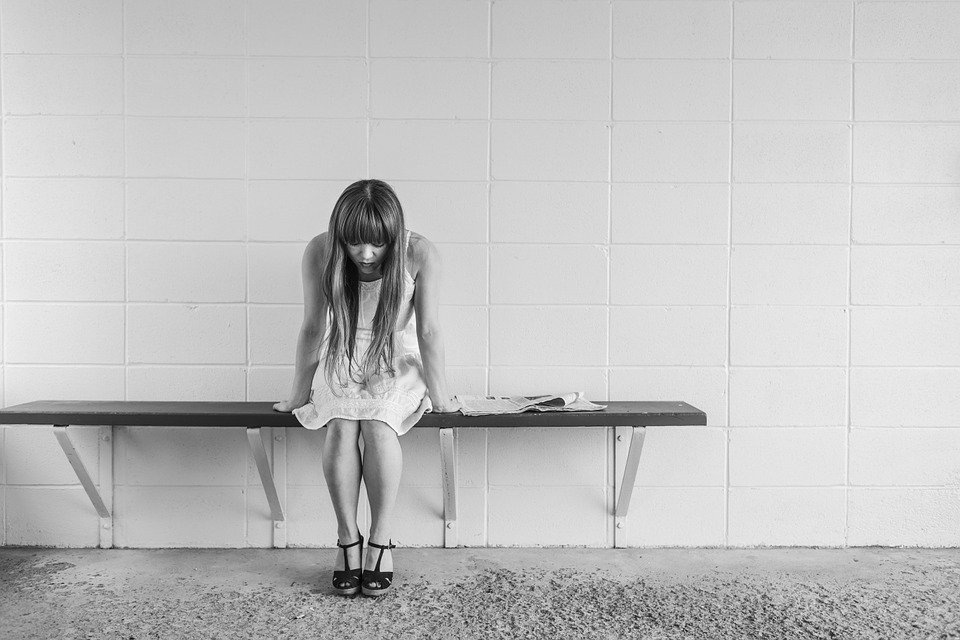 a sad girl sitting on a bench all alone, looking lonely and isolated.